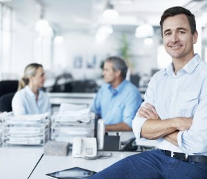 Confident businessman sitting on a desk with his coworkers in the background